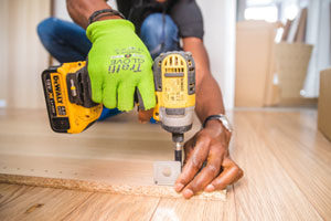 ouvrier du bâtiment en cours d'installation d'un isolant phonique sur le sol